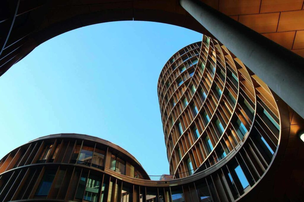 low-angle shot of curved buildings - green building
