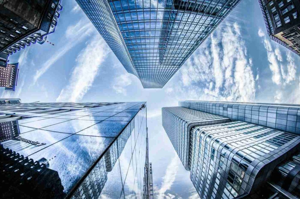 low angle shot of glass buildings - why build green