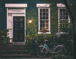 close up of ivy covered house with bicycle - how to price a green home