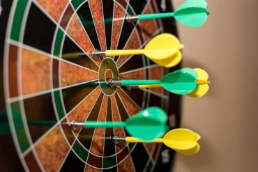 green and yellow darts on board - tips for creating a sustainable games room