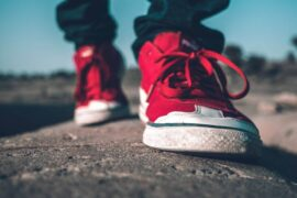 close up of person wearing red shoes while walking - how to live green on the go