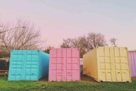 pastel shipping containers on grass - how to make the most of your space in a shipping container home