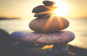 sunlight behind stack of pebbles - how solar energy adds value to your home