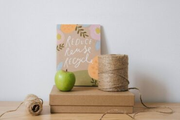 box, string and apple with reduce, reuse, recycle sign - how to be less wasteful at home with zero-waste