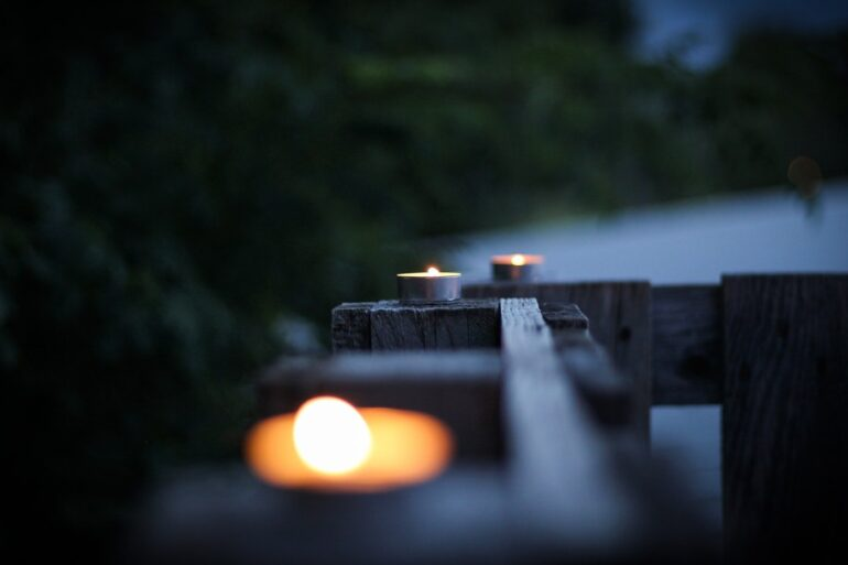 tealight candles burning on fence - best non toxic environmentally friendly candles