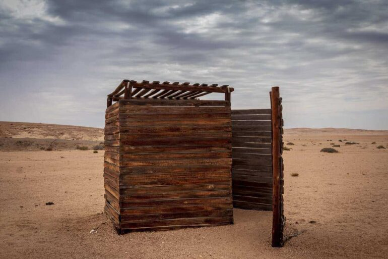 outhouse in desert under grey sky - how to build a diy composting toilet