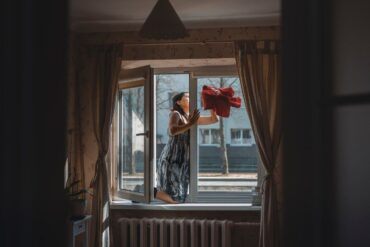 woman cleaning window with t-shirt - are green cleaning methods sustainable