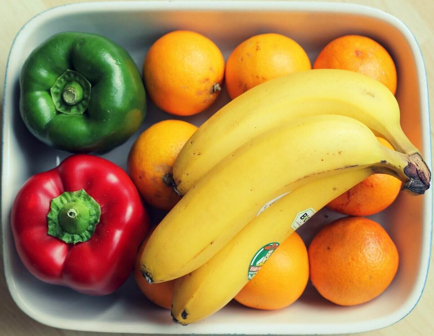 bananas oranges and peppers in dish - 5 ways reducing food waste can help save the environment