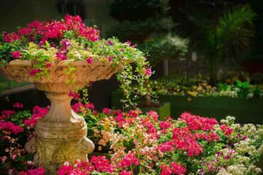 tall stone planter with pink flowers in garden - top innovative ideas to make your garden stand out