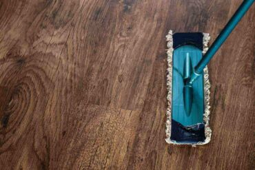 top view of dry mop on wooden floor - tips for cleaning your house the eco-friendly way