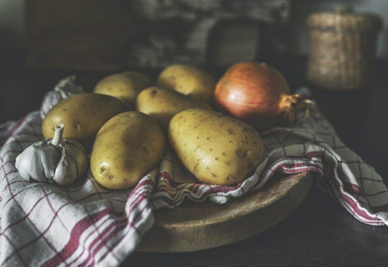 potatoes, onion and garlic on kitchen towel - which types of vegetables can be grown indoors