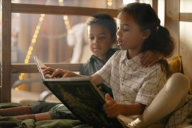 sister reading to brother in bunk bed - eco-friendly ways to update your childrens room