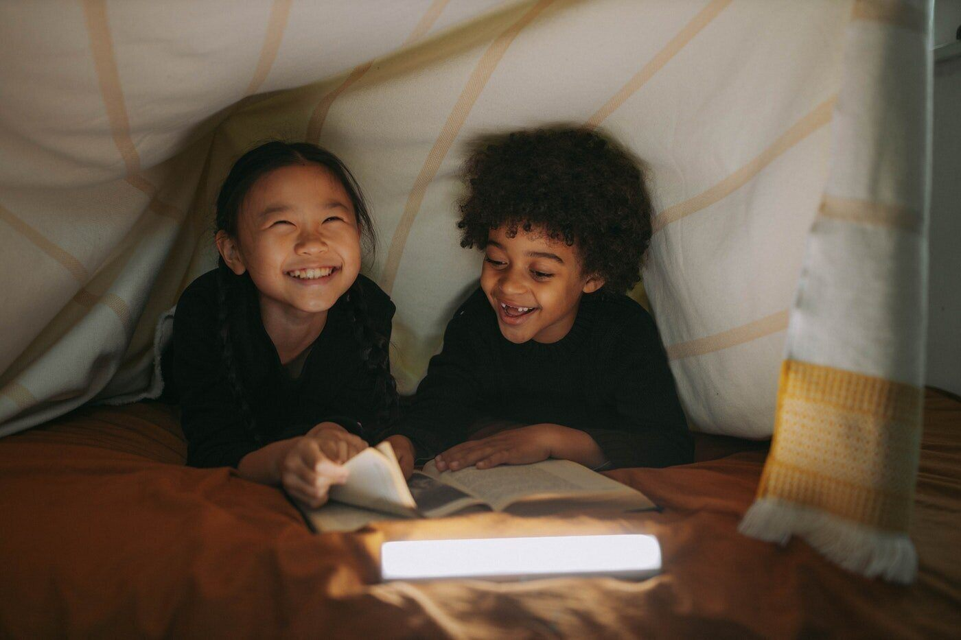 two kids reading under blanket - eco-friendly ways to update your childrens room